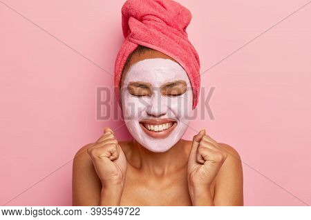 Headshot Of Energized Happy Dark Skinned Woman Wears Clay Mask On Face, Wrapped Towel On Hair, Smile