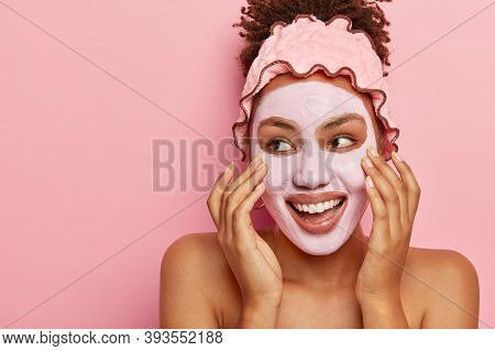 Spa And Skin Care Concept. Pleased Afro American Woman Applies Nourishing Clay Mask On Face, Has Gla