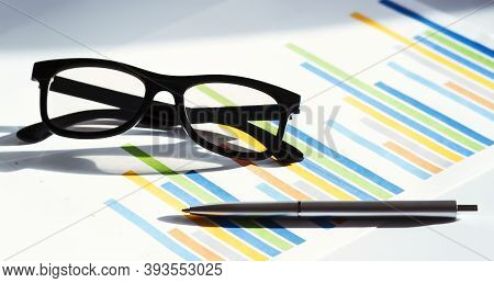 Business Concept With Glasses Pen And On Documents. Business Grafs And Charts