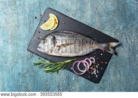 Fresh Fish Dorada Or Gilt-head Bream On Slate Board With Spices And Lemon