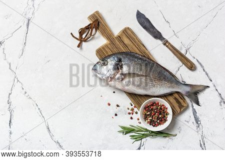 Fresh Fish Dorada Or Gilt-head Bream On Cutting Board With Spices