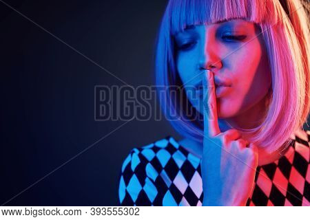 Portrait Of Young Girl With Blond Hair In Red And Blue Neon In Studio.