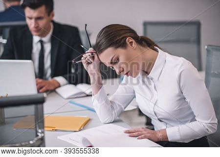 Young Business Woman Reading Document In Office.