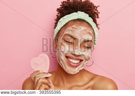 Beautiful Optimistic Afro American Woman Cleanses Face With Foam, Refreshes Skin, Has Well Cared Com