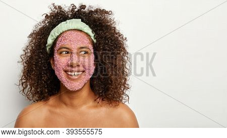 Pleasant Looking Cheerful Young Girl With Afro Hairstyle, Applies Pink Salt Granules On Face, Has So
