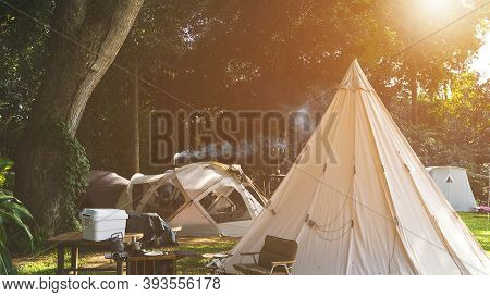 Field Tents Group And Wooden Table Set With Outdoor Kitchen Equipment In Camping Area At Natural Par