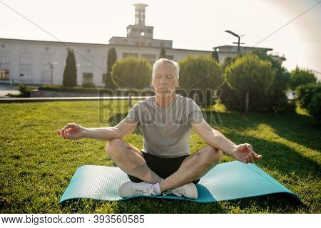 Grey-haired Man Sitting In Lotus Pose With Hands In Gyan Mudra