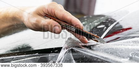 Car Wrapping Specialist Putting Vinyl Foil Or Film On Car. Protective Film. Applying A Protective Fi