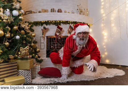 Santa Claus Climbs Out Of The Fireplace To Put Gifts Under The Tree. Surprised Santa Claus. Christma