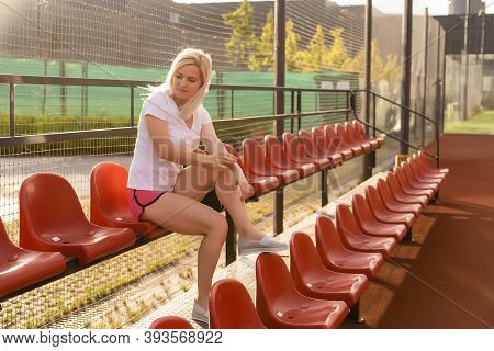 Young Blond Woman Sitting On The Stairs On Stadium Tribune, Relaxing After Training. Sportswoman On