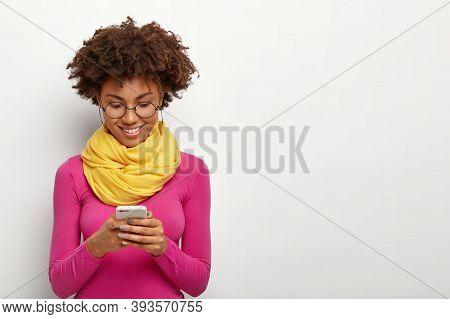 Horizontal Shot Of Pleased Dark Skinned Female Holds Modern Mobile Phone, Focused Into Display, Wear