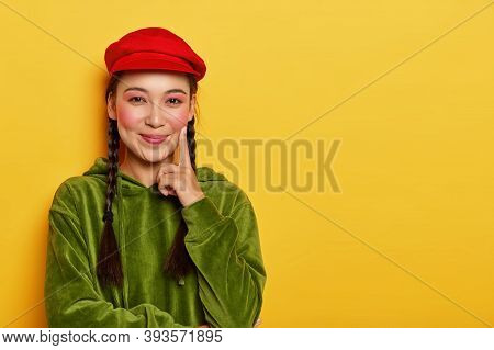 Horizontal Shot Of Glad Asian Girl Keeps Index Finger On Cheek, Looks Happily At Camera, Has Rouge C