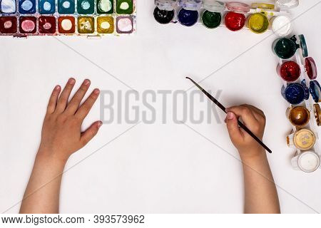 Top View Of Children's Hands While Drawing Gouache On Paper. The Child Starts Drawing A Child's Draw