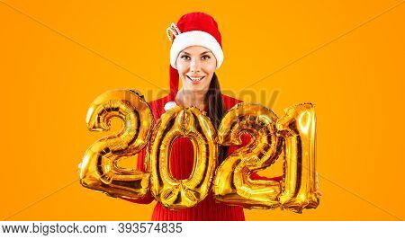 New Year 2021 Gold Balloons. Young Woman In Santa Claus Hat Having Smiling Holding In Hand 2021. Gir