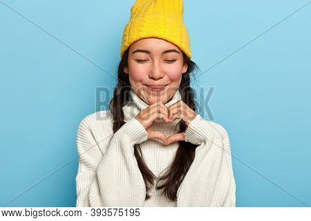 Cropped Image Of Beautiful Brunette Woman With Plaits Shares Deep Pure Feelings, Wears Yellow Hat An