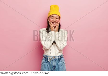 Attractive Young Korean Woman Touches Cheeks, Has Satisfied Expression, Keeps Eyes Shut, Feels Shy,