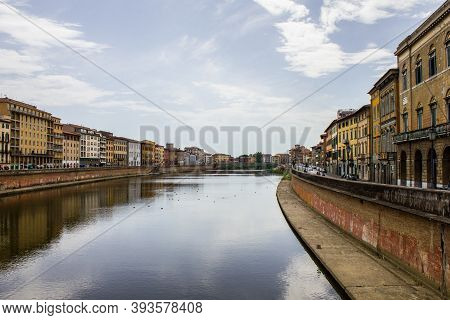 Pisa, Italy - July 9, 2017: View Of People Walking Along Arno River On A Summer Day