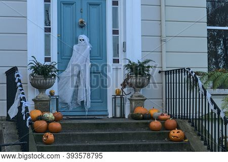 Spooky And Beautiful Halloween Decoration With Many Pumpkins, Burning Candle On The Stairs And Ghost