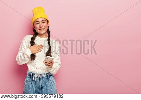 Portrait Of Pleased Korean Woman Keeps Palm On Chest, Being Touched By Heartwarming Words, Holds Mod