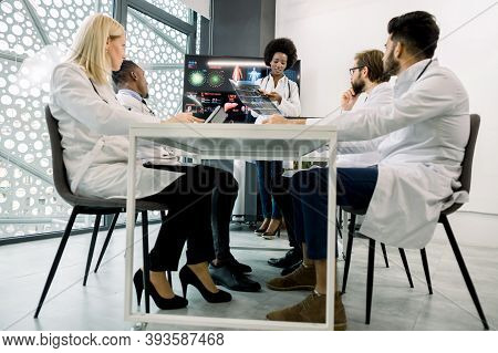 Pretty Young African Female Doctor In Meeting Room With Multiethnic Medical Team Of Specialists, Dis