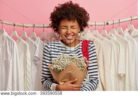 Image Of Overjoyed Curly Haired Woman In Striped Jumper, Spends Spare Time In Garment Shop, Chooses