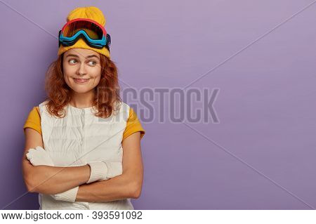 Indoor Shot Of Happy Redhead Woman Keeps Hands Crossed, Wears Yellow Hat And White Vest, Enjoys Wint
