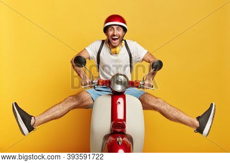 Funny Male Motorbike Driver Poses On Scooter, Keeps Legs Sideways, Wears Protective Helmet, White T
