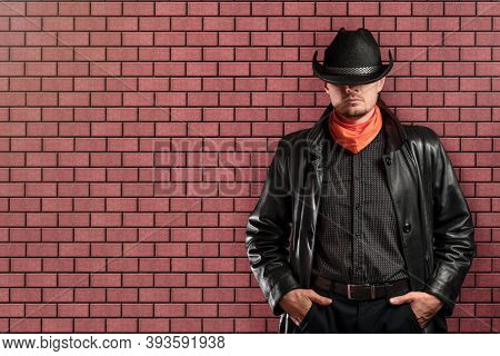 Man In A Hat And A Raincoat Against The Background Of A Red Brick Wall. Concept Of Indifference, Den