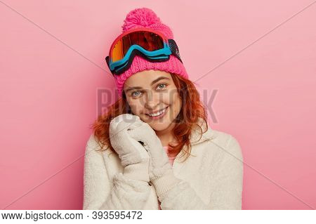 Portrait Of Lovely Cheerful Redhead Woman Wears Soft Mittens, Winter White Jumper, Pink Hat With Pom