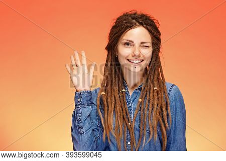 Funny And Joyful Winking Young Woman With Dreadlocks And Greeting Gesture.