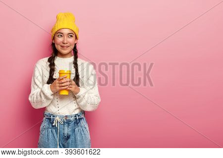 Dreamy Chinese Woman Drinks Takeaway Coffee, Stands Thoughtfully Against Pink Background, Wears Whit