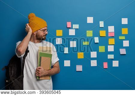 Serious Hipster Rubs Head, Looks Seriously At Colorful Notes Stuck On Wall, Recalls Necessary Inform