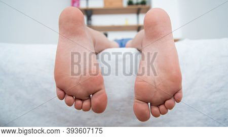 The Childs Feet Hanging From The Bed. The Child Is Lying On The Bed. Healthy Feet, No Signs Of Flat