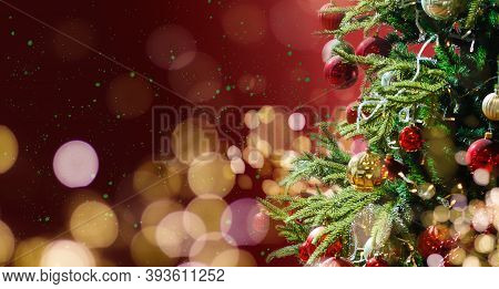 Decorated With Ornaments And Lights Christmas Tree On Red Background. Merry Christmas And Happy Holi