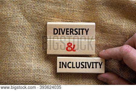 Wooden Blocks Form The Words 'diversity And Inclusivity' On Canvas Background. Male Hand. Business,