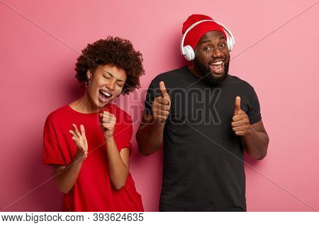 Afro American Couple Have Happy Relaxed Faces, Catch Tune And Like Track, Have Fun On Party, Enjoys