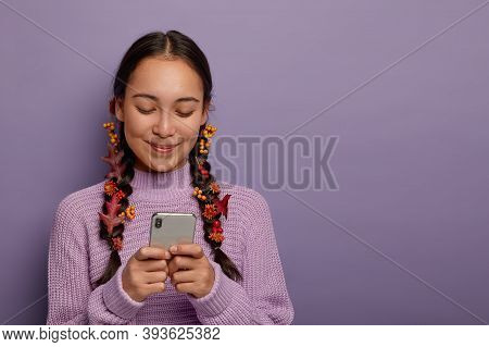 Lovely Millennial Brunette Woman Has Two Plaits With Stuck Autumn Leaves As Natural Cosmetics, Enjoy