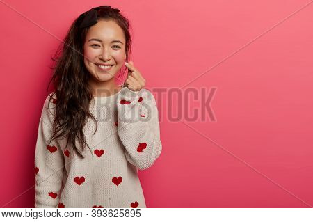Romantic Chinese Woman Shows Korean Heart Sign With Two Fingers Crossed, Smiles Joyfully And Confess