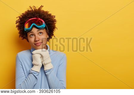 Pensive Curly Female Skier Wears Warm Blue Jumper And White Mittens, Thinks About Winter Rest, Enjoy