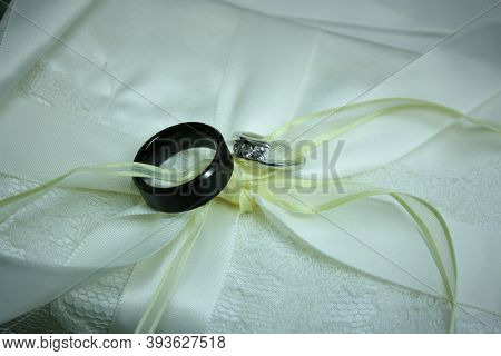 Wedding Rings Entwined In Satin Ribbon On Top Of Satin Background