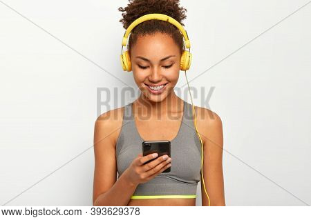 Glad Sporty Curly African American Woman Listens Music In Headphones, Updates Her Playlist, Enjoys F