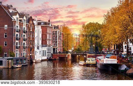 Amsterdam, Netherlands. Panoramic view of autumn Dutch city. Famous channel of Amstel river. Evening cityscape. Colorful sunset scene of famous travel destination in Europe. Romantic traveling place.