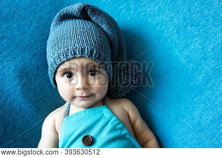 Cute Newborn Baby In The Blue Hat. Happy Baby On A Blue Background. Closeup Portrait Of Newborn Baby