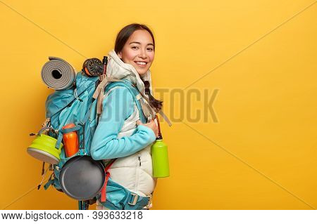 Positive Asian Female Hiker Stands Sideways To Camera, Carries Big Rucksack With Necessary Things Fo