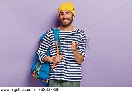 Photo Of Glad Smiling Man Traveler Points At You With Index Finger, Carries Rucksack With Necessary