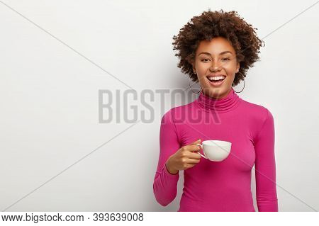 Photo Of Glad Young African American Woman Wears Pink Poloneck, Holds Mug With Coffee, Enjoys Spare