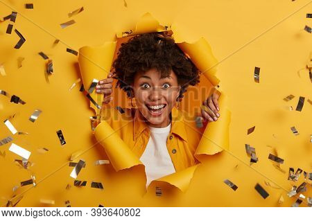 Close Up Shot Of Overjoyed Afro American Female Stands In Ripped Hole Of Yellow Background, Dressed