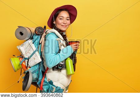 Pleased Young Asian Female Traveler Stops On Her Way To Have Coffee Break, Wears Hat And Casual Outf