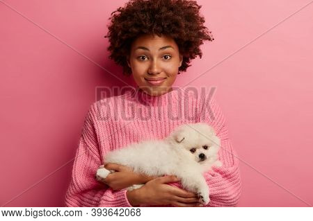Positive Delighted African American Woman Poses With Her Four Legged Friend, Hears Advice How To Fee