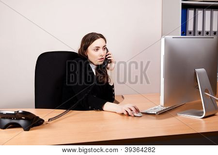 Business Woman Working On Her Computer  And Calling By Phone